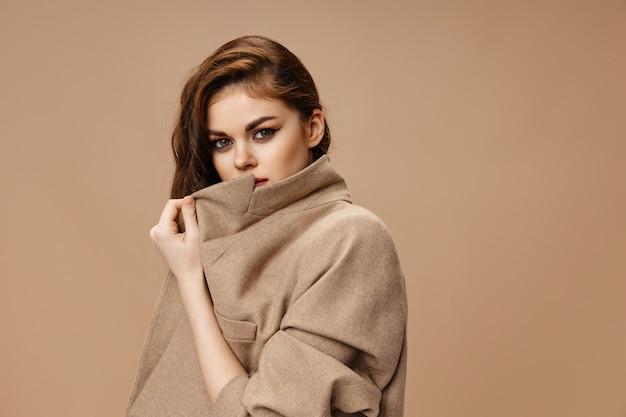 Retrato de mulher com casaco bege com gola e penteado do modelo vista recortada