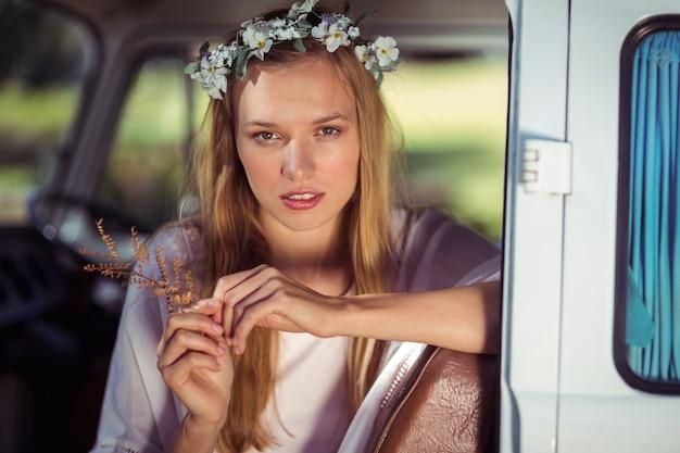 Retrato de mulher com coroa de flores, sentado na caravana
