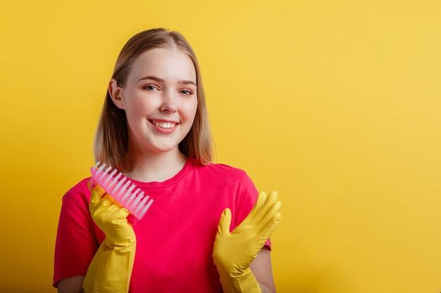 Retrato de mulher com escova de limpeza em luvas de borracha. jovem loira feliz sorridente mulher pronta para limpar a casa com suprimentos domésticos isolados sobre fundo de cor amarela. copie o espaço.