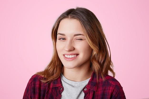 Retrato de mulher com expressão alegre, pisca os olhos como flerta com homem bonito, expressa sua simpatia, vestida com camisa xadrez casual, isolada em rosa. a mulher pisca interior