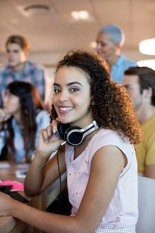 Retrato de mulher com fones de ouvido trabalhando com sua equipe no escritório