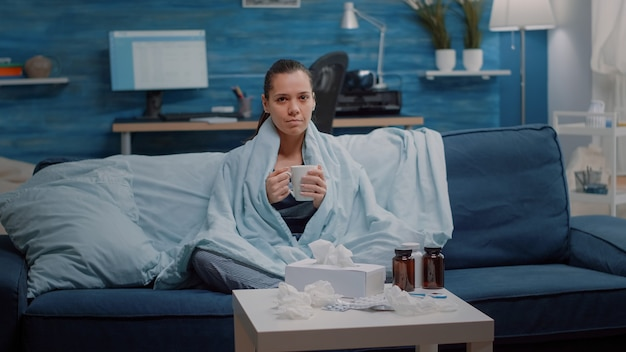 Retrato de mulher com gripe segurando uma xícara de chá no cobertor