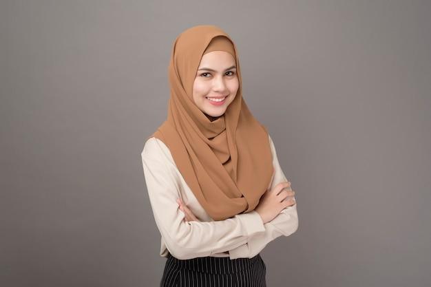 Retrato de mulher com hijab está sorrindo em cinza