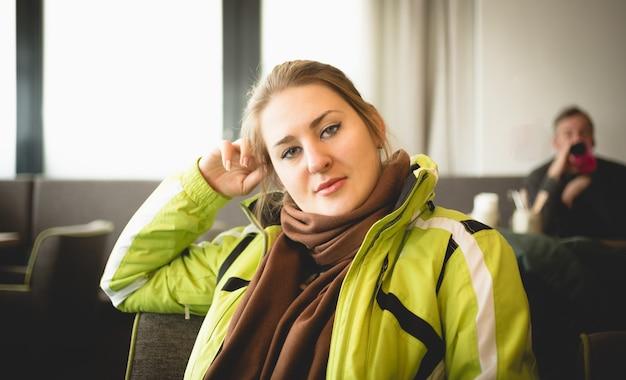Retrato de mulher com jaqueta de esqui relaxando em um restaurante no topo da montanha
