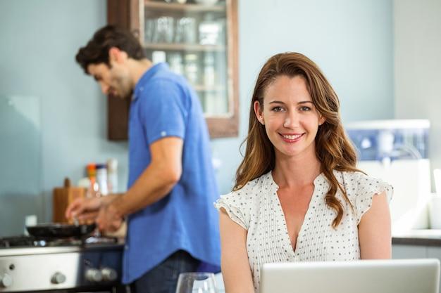 Retrato de mulher com laptop na cozinha