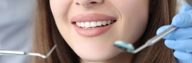 Retrato de mulher com lindos dentes brancos em consulta com o dentista