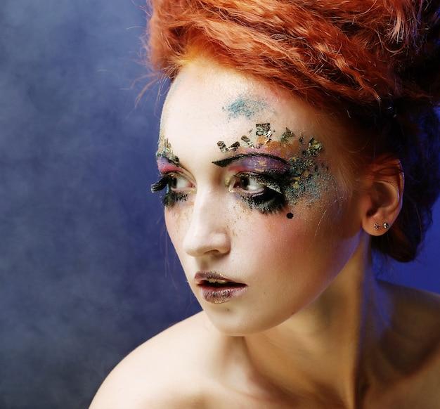 Retrato de mulher com maquiagem artística sobre fundo de fumaça