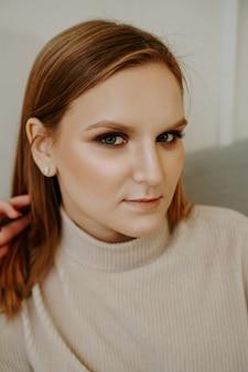 Retrato de mulher com maquiagem brilhante e traços faciais rígidos, vestida com um suéter bege, sentada na cama