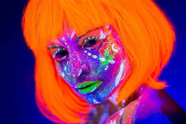 Retrato de mulher com maquiagem de néon. tinta fluorescente em luz ultravioleta