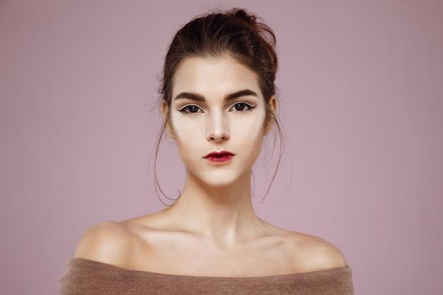 Retrato de mulher com maquiagem posando em rosa