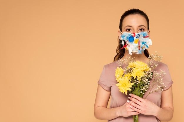 Retrato de mulher com máscara artesanal segurando buquê de flores
