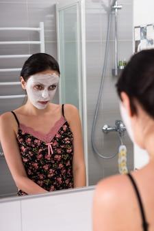 Retrato de mulher com máscara cosmética no rosto, olhando-se no espelho no banheiro moderno de azulejos de casa