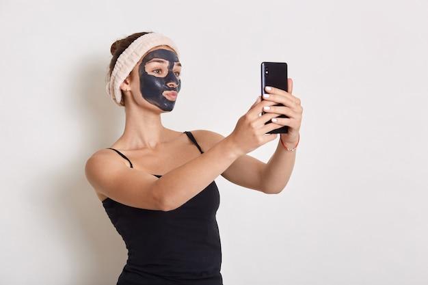 Retrato de mulher com máscara cosmética preta no rosto, segurando um telefone inteligente moderno na mão e olhando para a tela do dispositivo