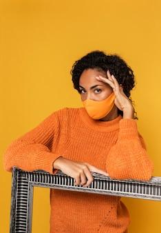 Retrato de mulher com máscara posando com moldura