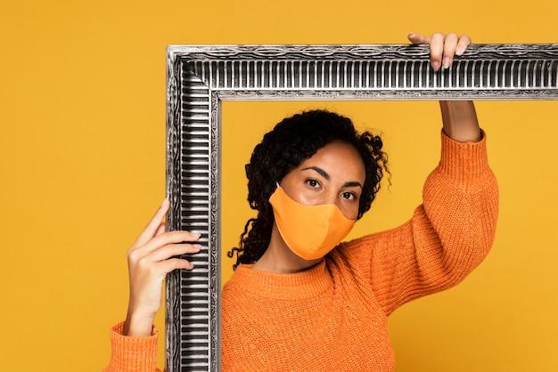 Retrato de mulher com máscara segurando moldura