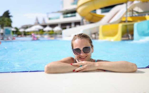 Retrato de mulher com óculos de sol no parque aquático na piscina