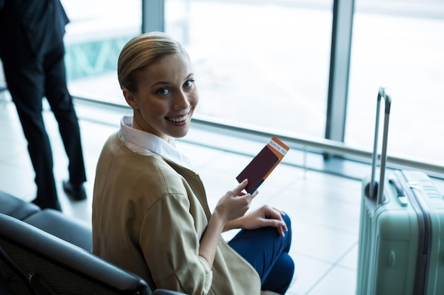 Retrato de mulher com passaporte e cartão de embarque na área de espera