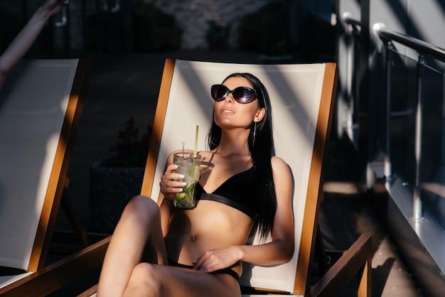 Retrato de mulher com perfeito corpo bronzeado ajuste usando óculos de sol da moda, beber coquetel