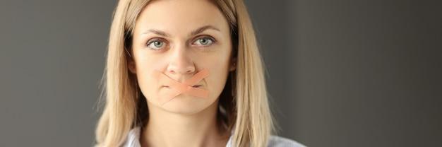 Retrato de mulher com psicologia da boca com fita adesiva do conceito de silêncio feminino
