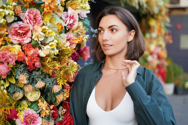 Retrato de mulher com ramo de flores ao pôr do sol na rua da cidade feliz positivo sorrindo