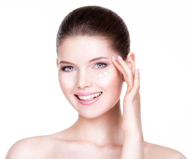 Retrato de mulher com rosto saudável, aplicação de creme cosmético sob os olhos.