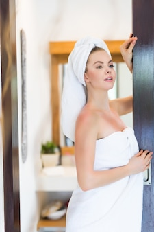 Retrato de mulher com roupão e toalha na cabeça em pé dentro de casa no banheiro