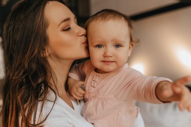Retrato de mulher com roupas brancas em casa e seu bebê de olhos azuis. a senhora beija a filha com amor.