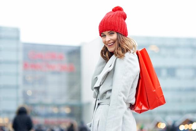 Retrato de mulher com sacolas de compras cheias de presentes maravilhosos