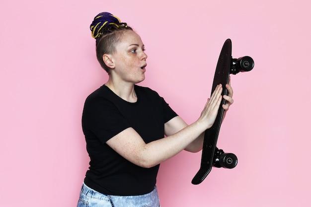 Retrato de mulher com skate nas mãos dela e olhando para ele.