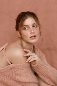 Retrato de mulher com suéter rosa e ombro nu