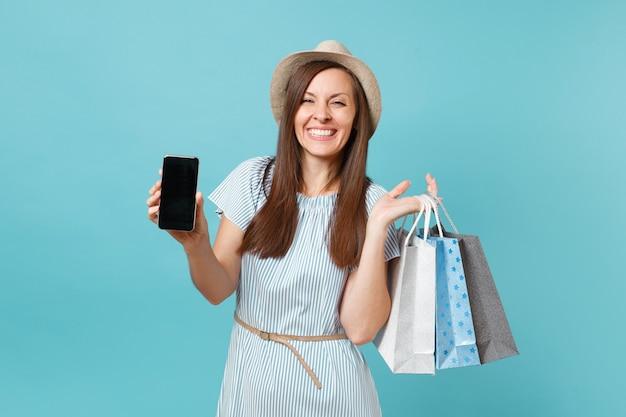 Retrato de mulher com vestido de verão, chapéu de palha segurando sacolas de pacotes com compras após as compras, celular móvel com tela vazia, isolada em fundo azul pastel. copie o espaço para anúncio.