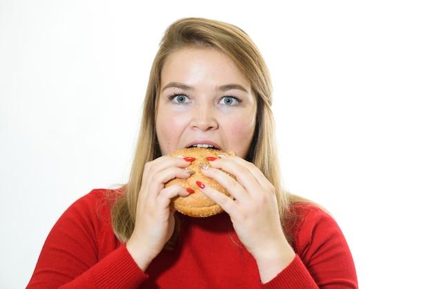 Retrato de mulher comendo hambúrguer