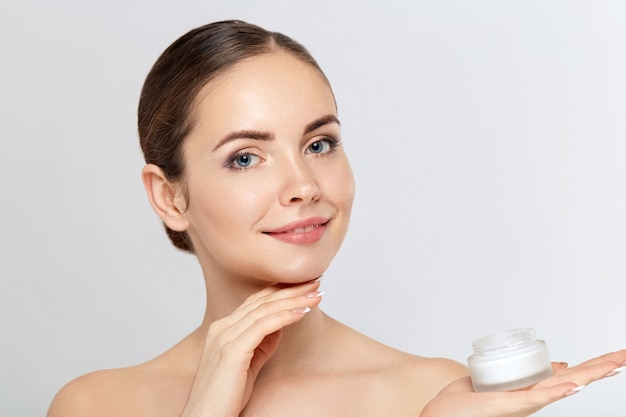 Retrato de mulher, conceito de cuidados com a pele, linda pele e mãos segurando e aplique o creme hidratante. tratamento facial. cosmetologia, beleza e spa.