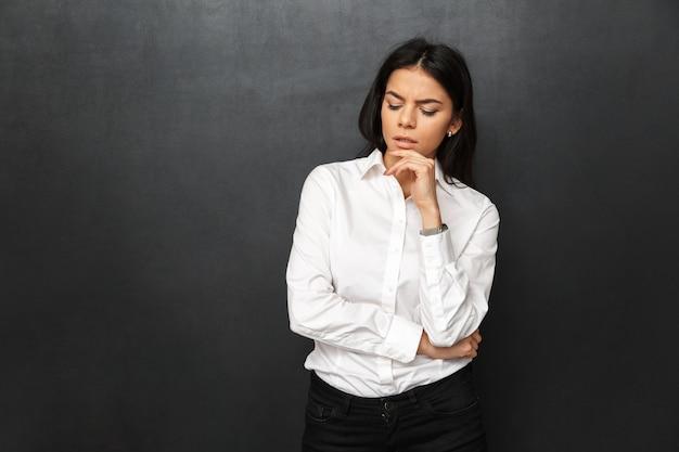 Retrato de mulher concentrada na casa dos 30 anos, com longos cabelos castanhos, vestindo roupas formais, pensando e tocando o queixo com olhar pensativo, isolado sobre uma parede cinza
