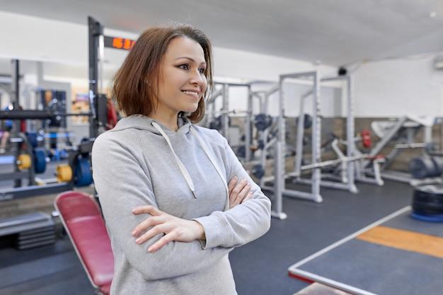 Retrato de mulher confiante de meia-idade com as mãos postas no ginásio