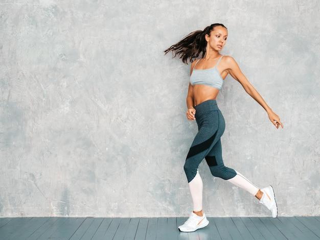 Retrato de mulher confiante fitness em roupas esportivas, olhando confiante. feminino posando no estúdio perto da parede cinza