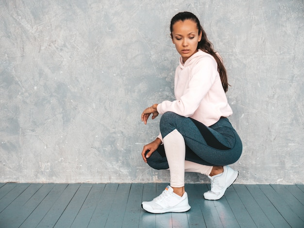 Retrato de mulher confiante fitness em roupas esportivas, olhando confiante. feminino sentado no estúdio perto da parede cinza