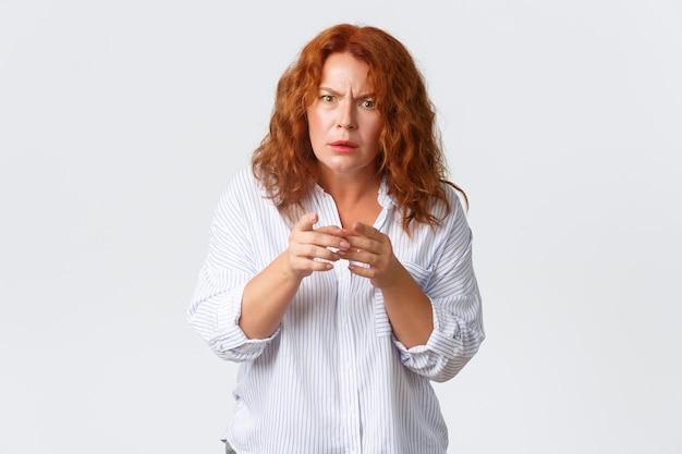 Retrato de mulher confusa ruiva de meia-idade olhando com descrença, não consigo entender algo, carrancudo e olhar perplexo, apontando o dedo hesitante, parede branca de pé.