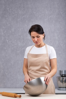 Retrato de mulher cozinheira na cozinha, avental de cozinha.