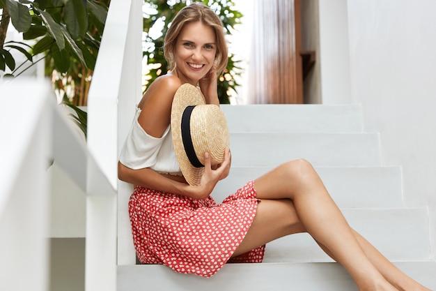 Retrato de mulher de aparência agradável usa blusa da moda e saia de bolinhas, segura um chapéu de palha, tem pernas delgadas, sorri com alegria, alegra-se com bom descanso nos trópicos. conceito de beleza e descanso