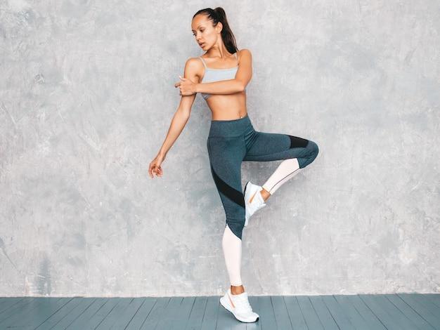 Retrato de mulher de aptidão em esportes roupas olhando confiante. jovem fêmea vestindo roupas esportivas. bela modelo com corpo bronzeado perfeito. feminino pulando no estúdio perto da parede cinza