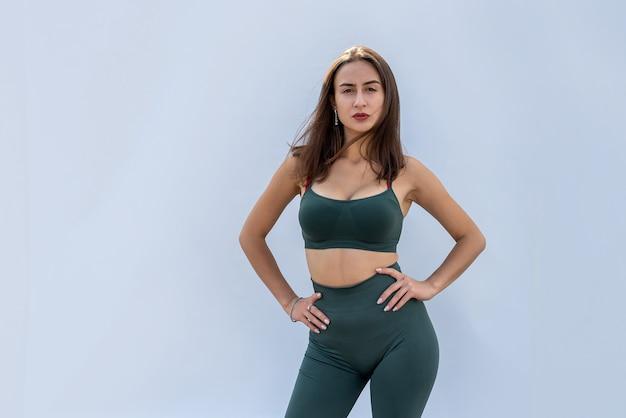 Retrato de mulher de aptidão em sportswear posando isolado em fundo cinza. conceito de saúde e esporte