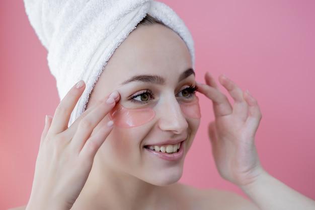 Retrato de mulher de beleza com tapa-olhos no fundo rosa. rosto de beleza de mulher com máscara sob os olhos. cuidados com a pele, conceito de produto cosmético