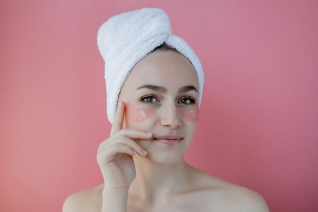Retrato de mulher de beleza com tapa-olhos no fundo rosa. rosto de beleza de mulher com máscara sob os olhos.