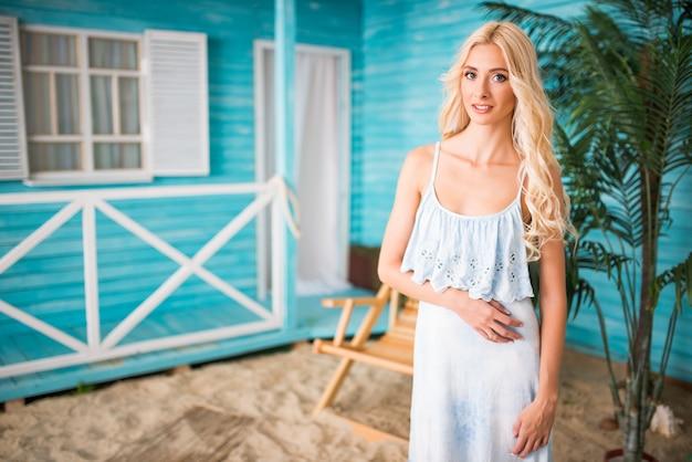Retrato de mulher de blusa azul posando perto de casa de praia