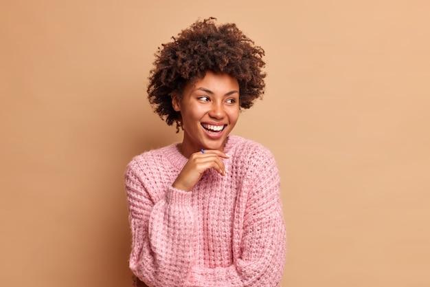 Retrato de mulher de cabelo encaracolado mantém a mão sob o queixo e desvia o olhar alegremente usando um macacão de malha e poses de expressão despreocupada contra a parede marrom