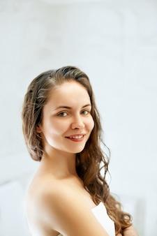 Retrato de mulher de cabelo molhado, conceito de cuidado de pele saudável de cabelo de beleza, bela modelo com cabelo molhado no banheiro.