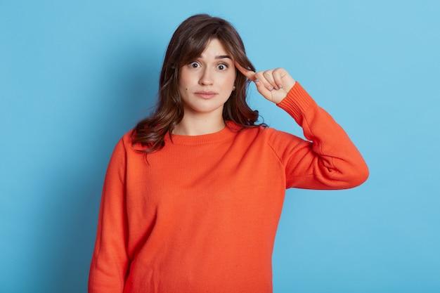 Retrato de mulher de cabelos escuros em jumper de estilo urbano faz sinal estúpido com o dedo perto da cabeça, gesticulando má mente, ideia maluca idiota, isolada na parede azul, aparência feminina com espanto