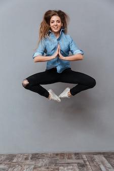 Retrato de mulher de camisa pulando no estúdio