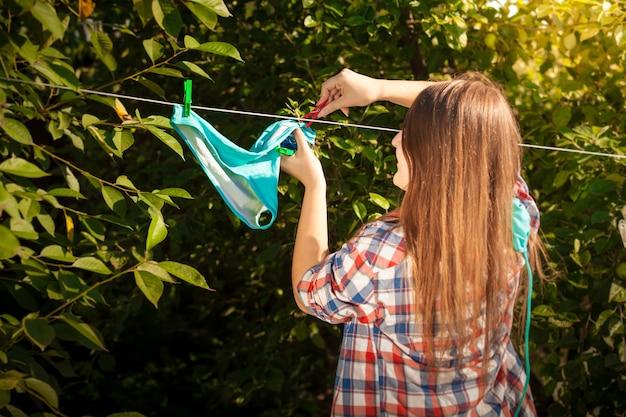 Retrato de mulher de camisa secando biquíni no varal